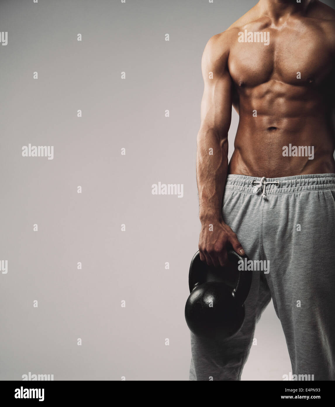 Cropped image of young man in sweatpants holding kettle bell. Crossfit workout theme on grey background work with - Stock Image