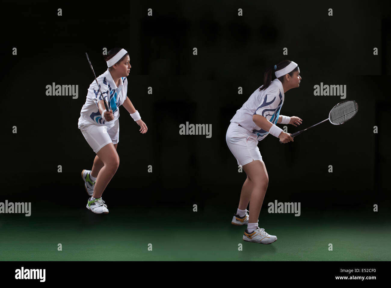 Profile shot of female players playing doubles badminton over black background - Stock Image
