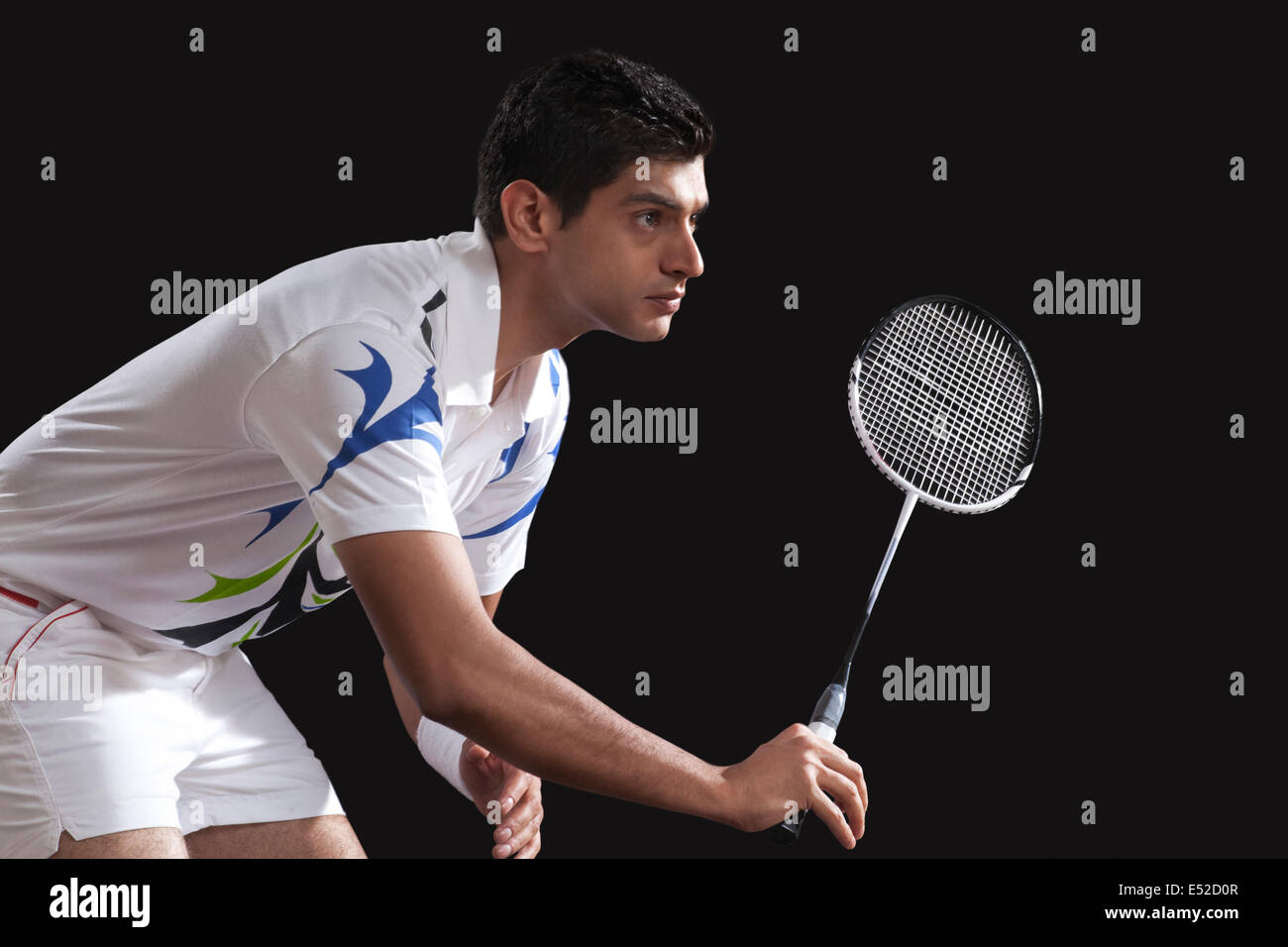 Young male player with racket playing badminton isolated over black background - Stock Image