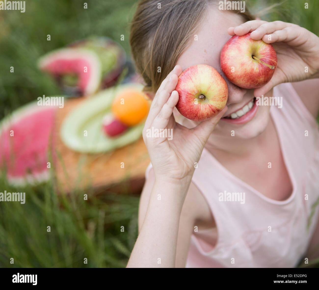 A girl holding two apples in front of her eyes - Stock Image