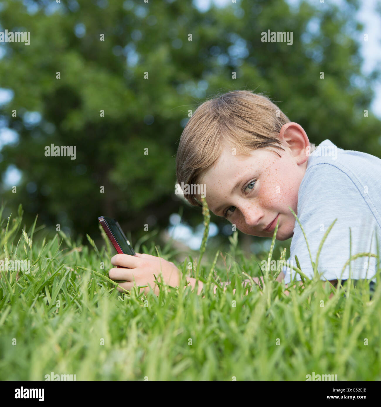 A young boy sitting on the grass using a hand held electronic games device. - Stock Image