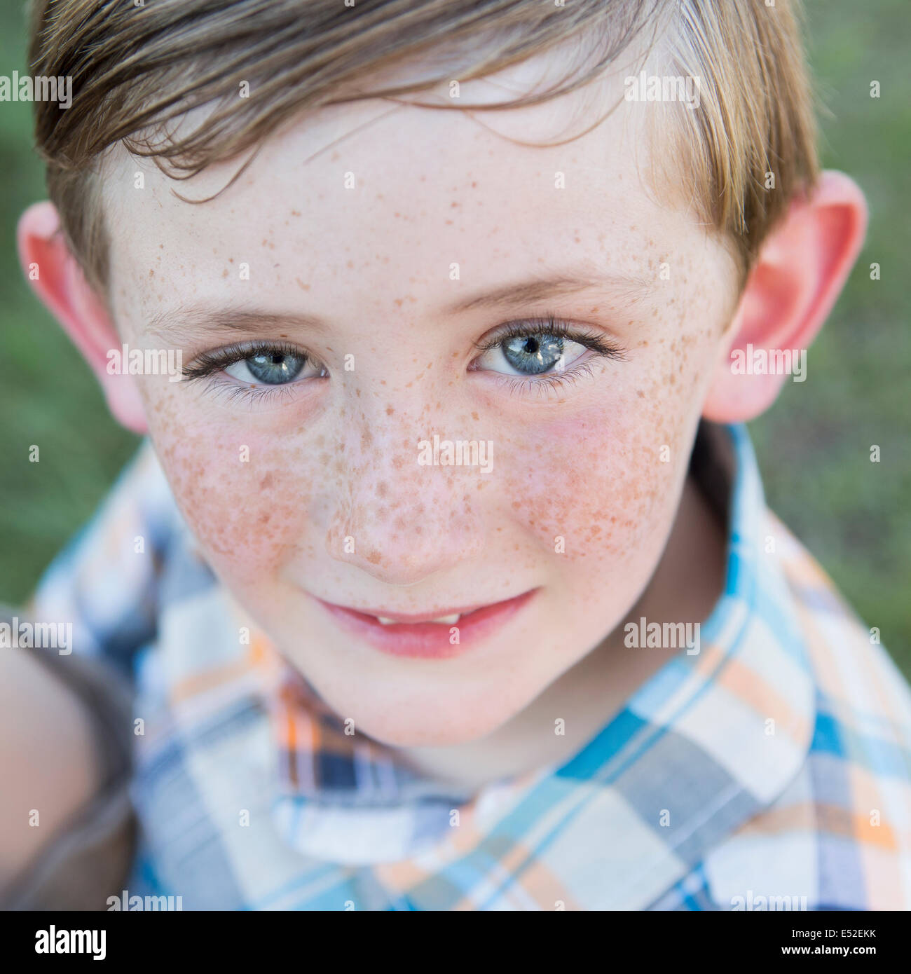 Portrait of a young boy with blue eyes and freckles on his nose. - Stock Image