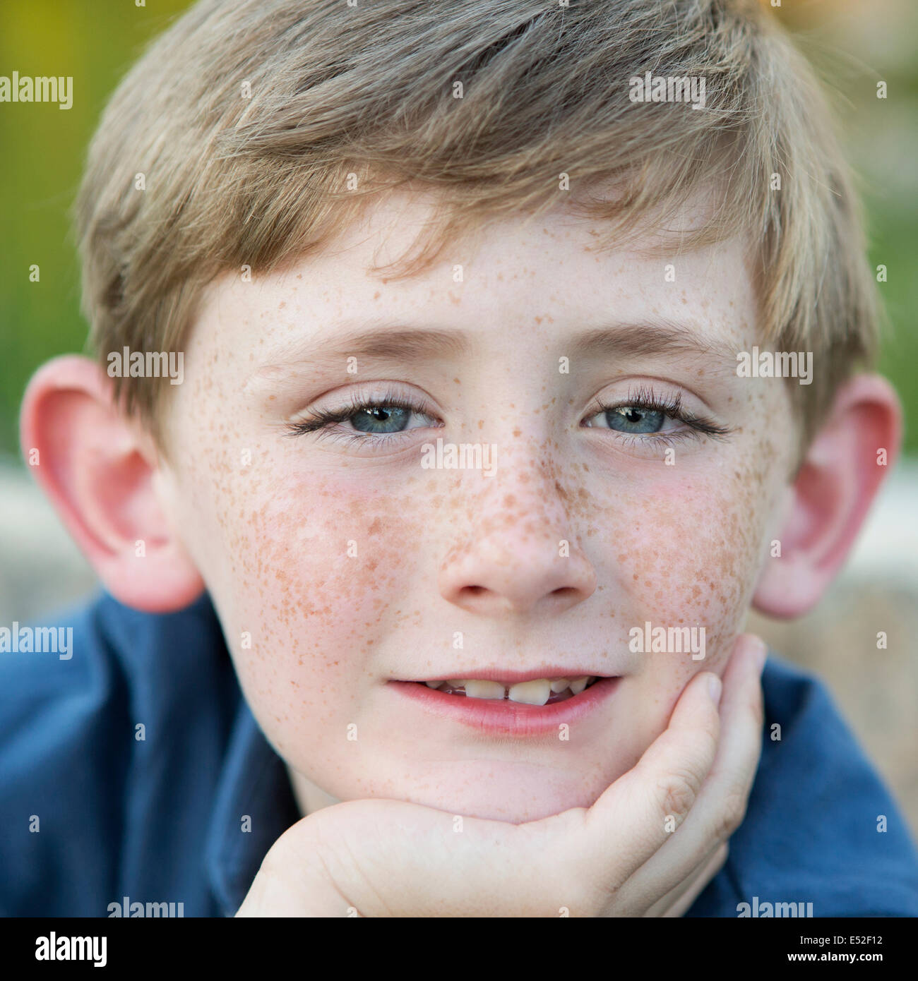 Head and shoulders portrait of a young boy sitting with his chin resting on his hand. - Stock Image