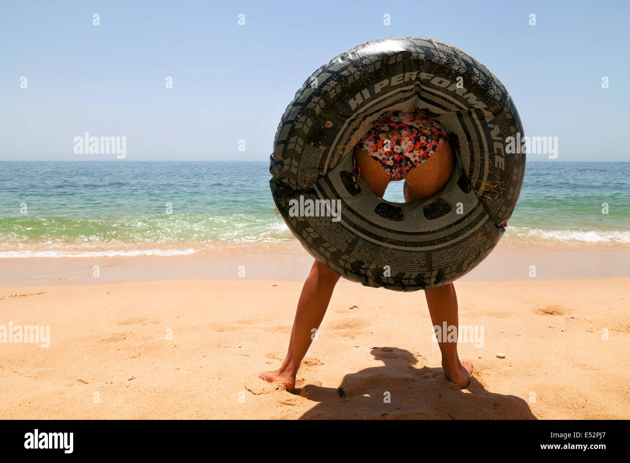 young-woman-standing-up-on-a-beach-with-a-rubber-ring-round-her-bottom-E52PJ7.jpg