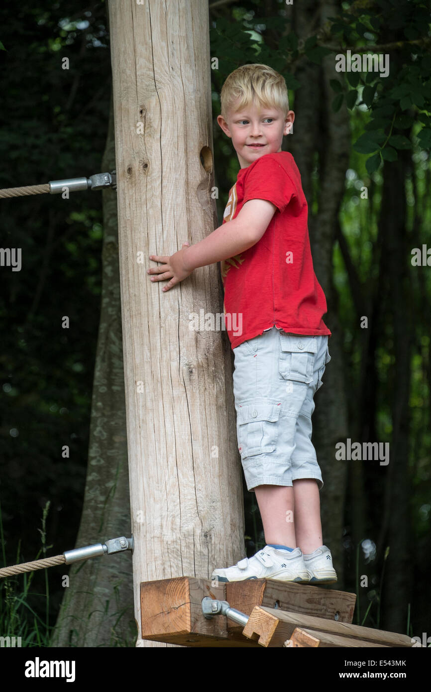 Boy aged six negotiates obstacle on adventure playground - Stock Image