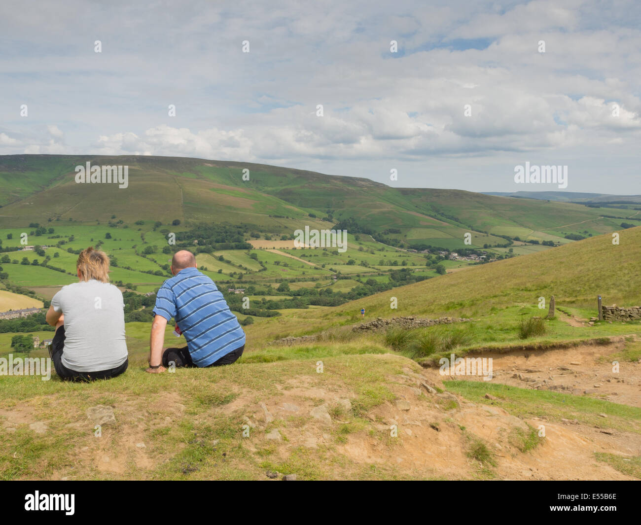 Two walkers admiring the view over Edale in the Peak District - Stock Image