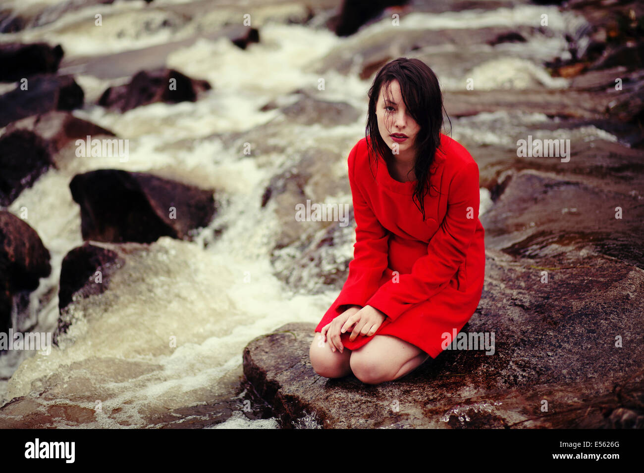 Young woman is sitting on a creek - Stock Image