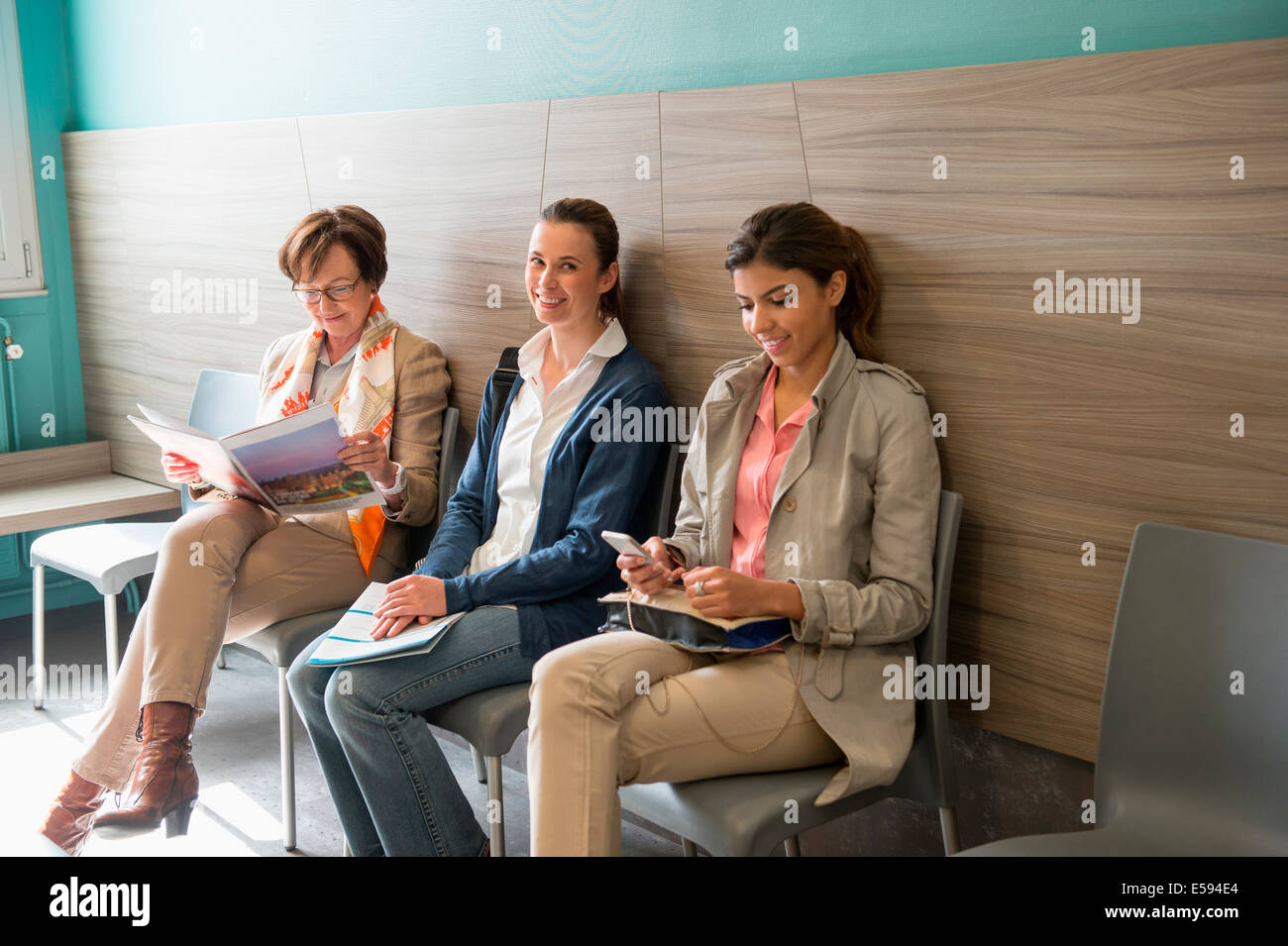 Three women in waiting area of hospital - Stock Image