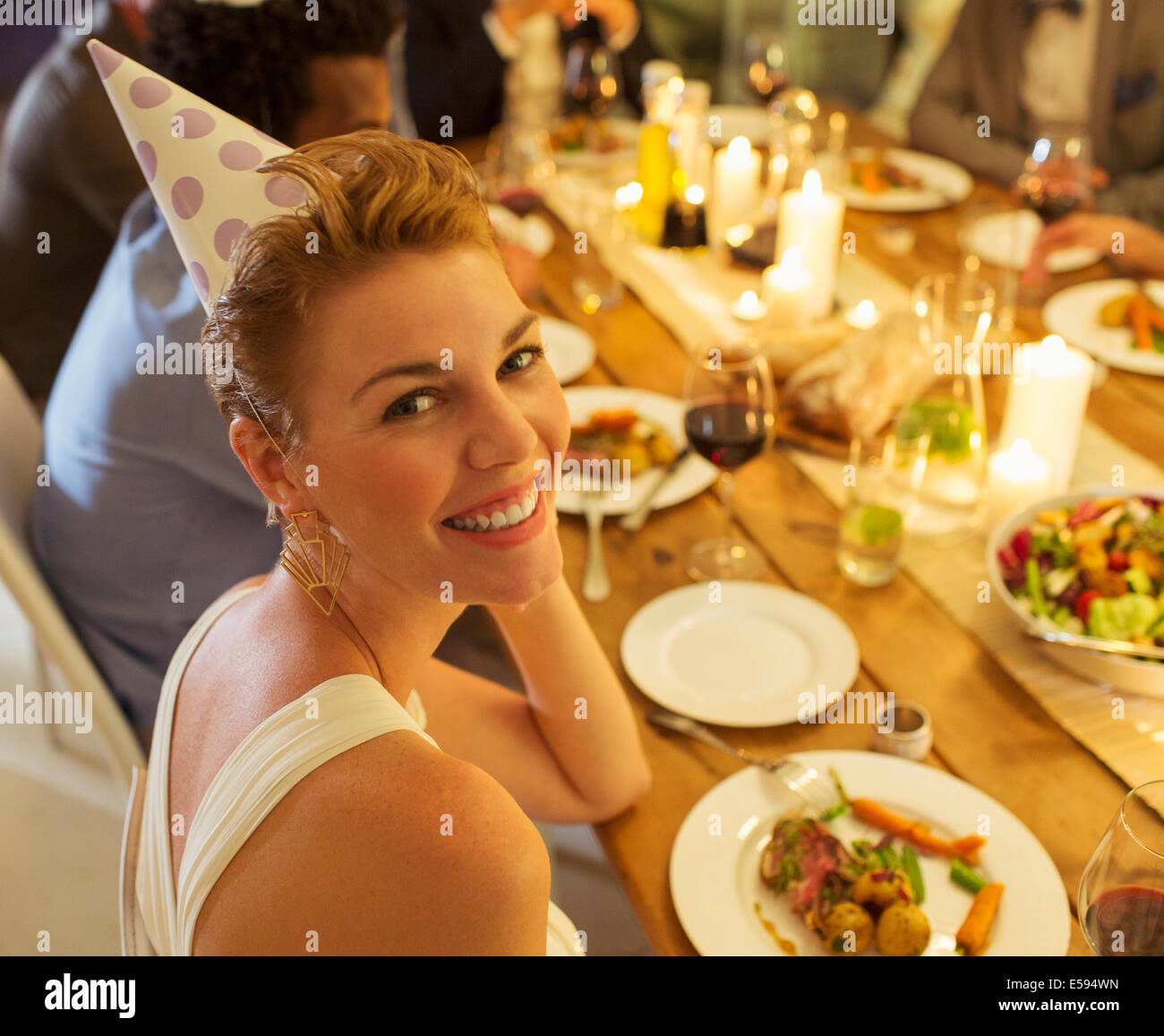 Woman smiling at birthday party - Stock Image