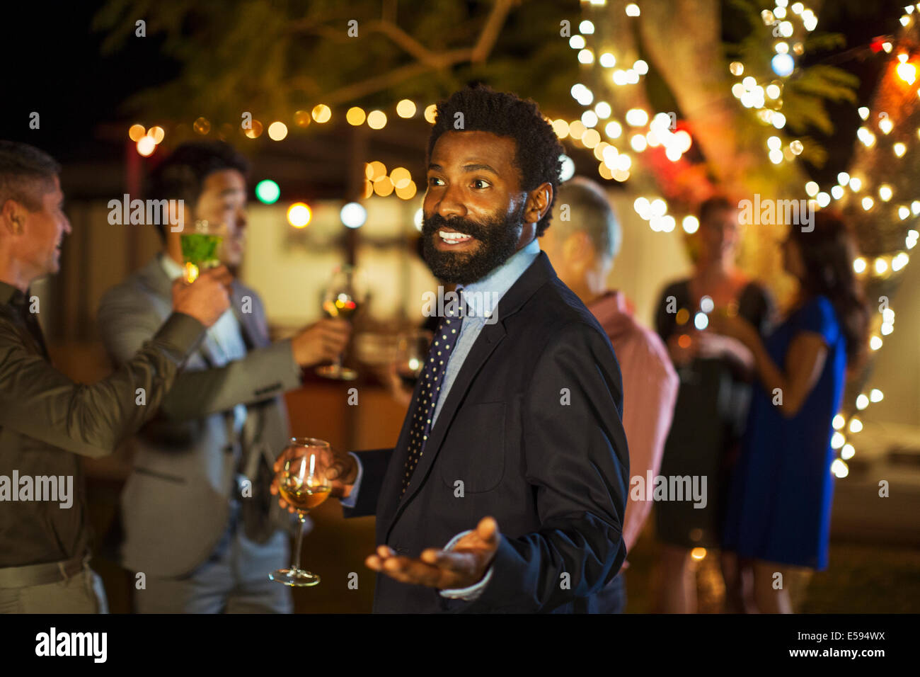 Man gesturing with wine at party - Stock Image