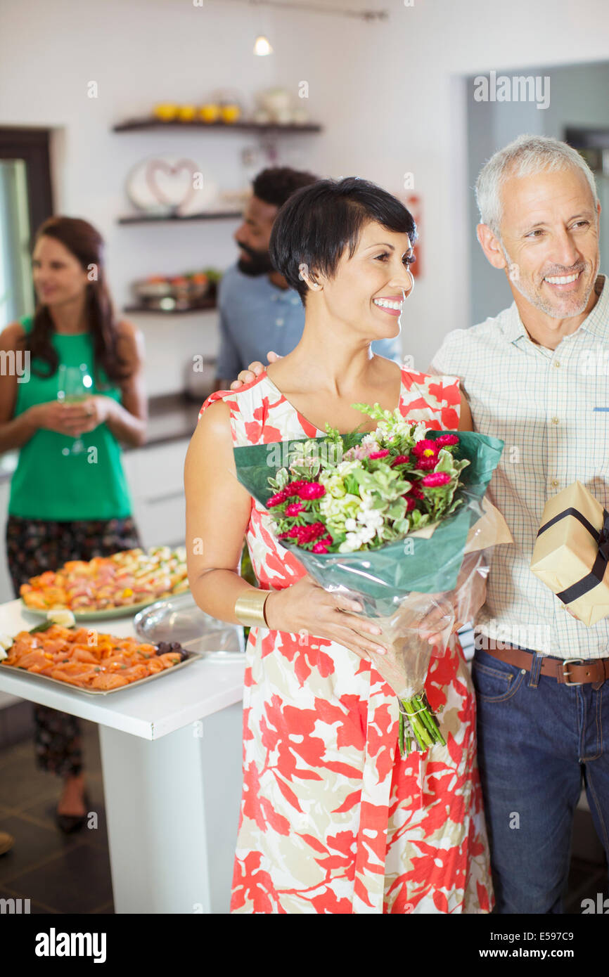 Couple carrying gifts at party - Stock Image