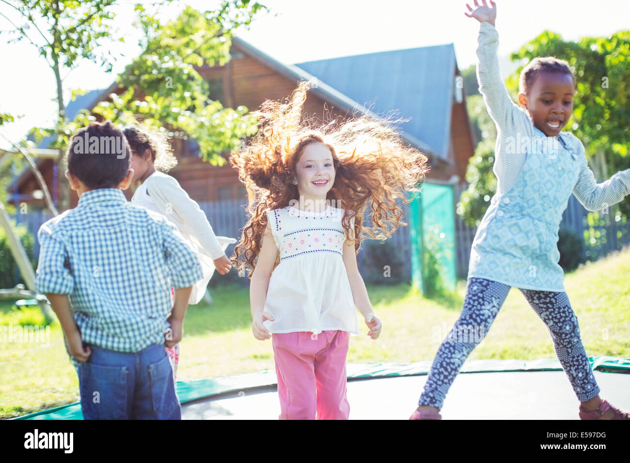 Children jumping on trampoline outdoors - Stock Image
