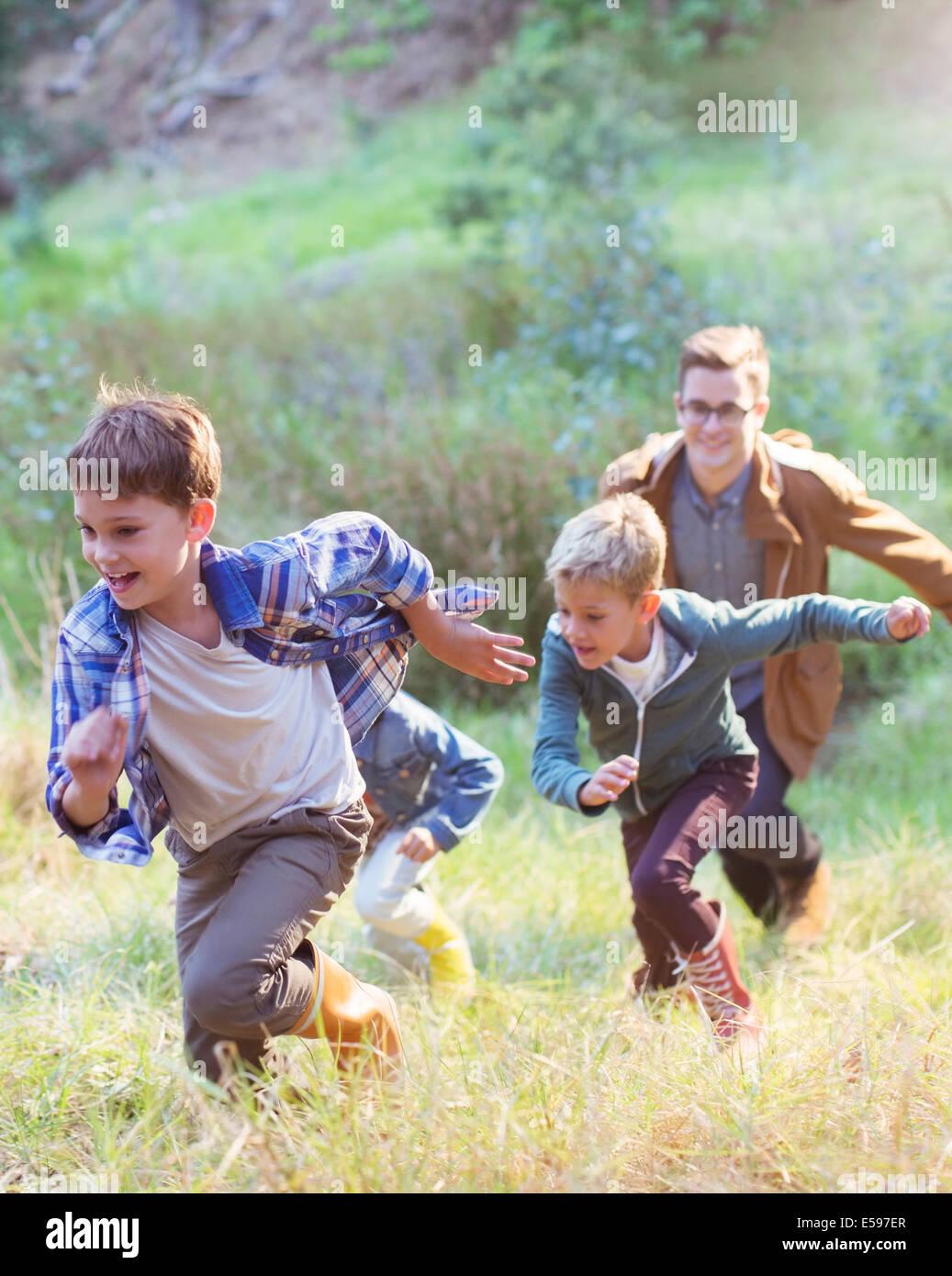 Boys running in field - Stock Image