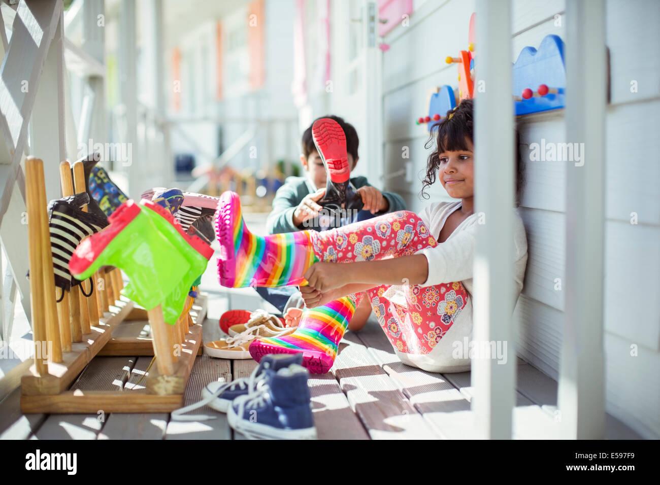 Children pulling on rainboots on porch - Stock Image