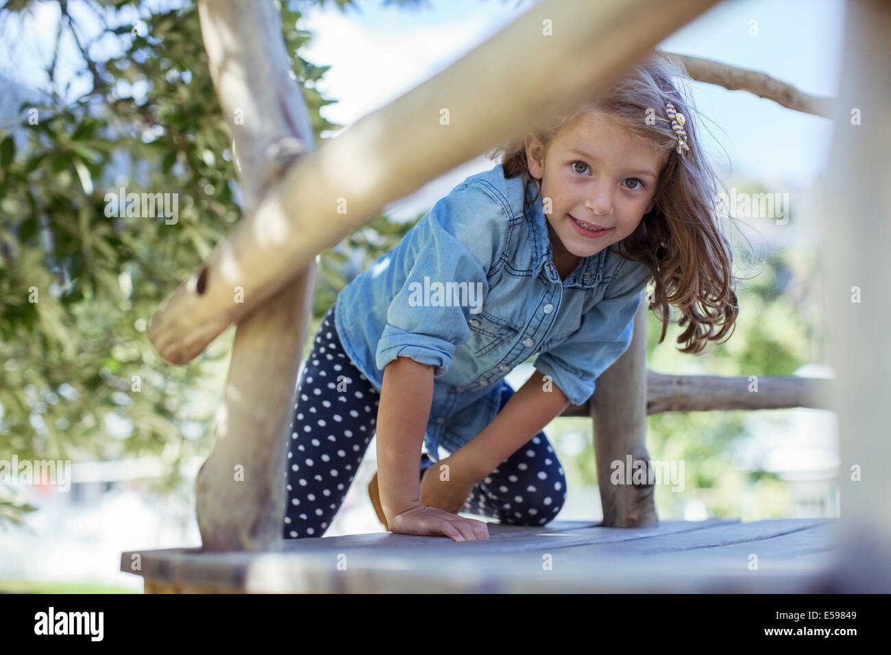 Girl climbing in treehouse outdoors - Stock Image