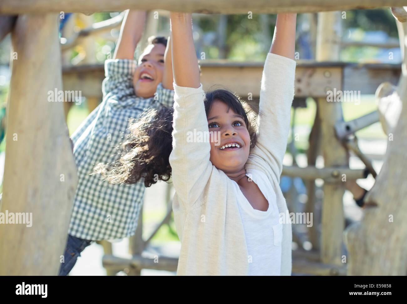 Children climbing on monkey bars - Stock Image