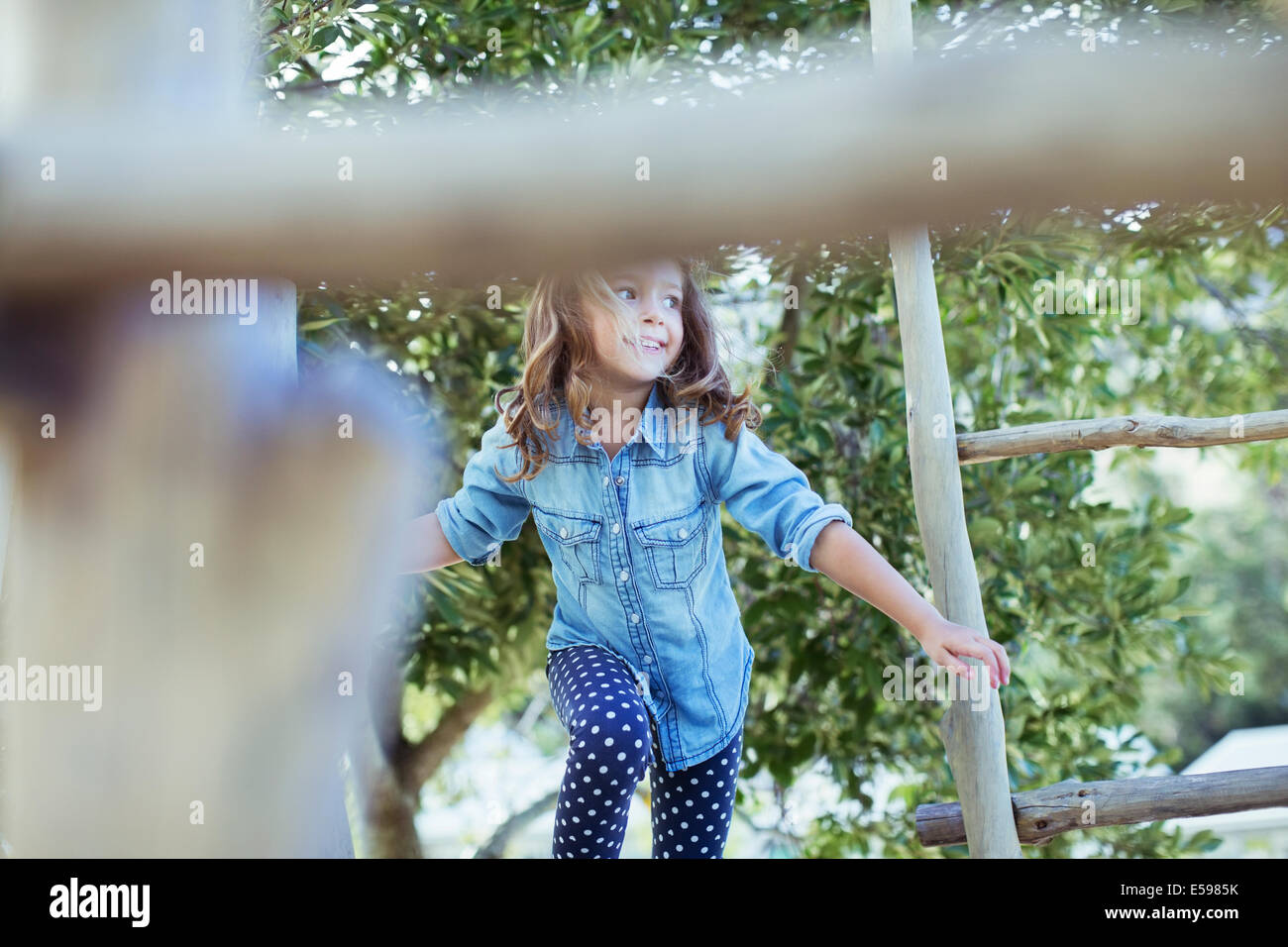 Girl climbing on play structure - Stock Image