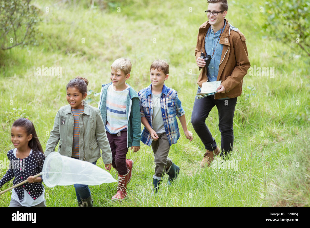 Students and teacher walking in field - Stock Image