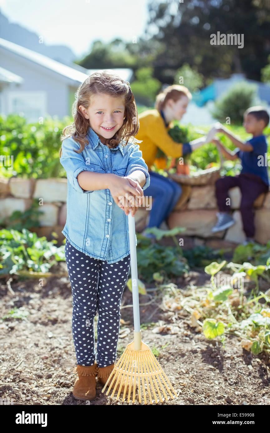 Girl holding rake in garden - Stock Image