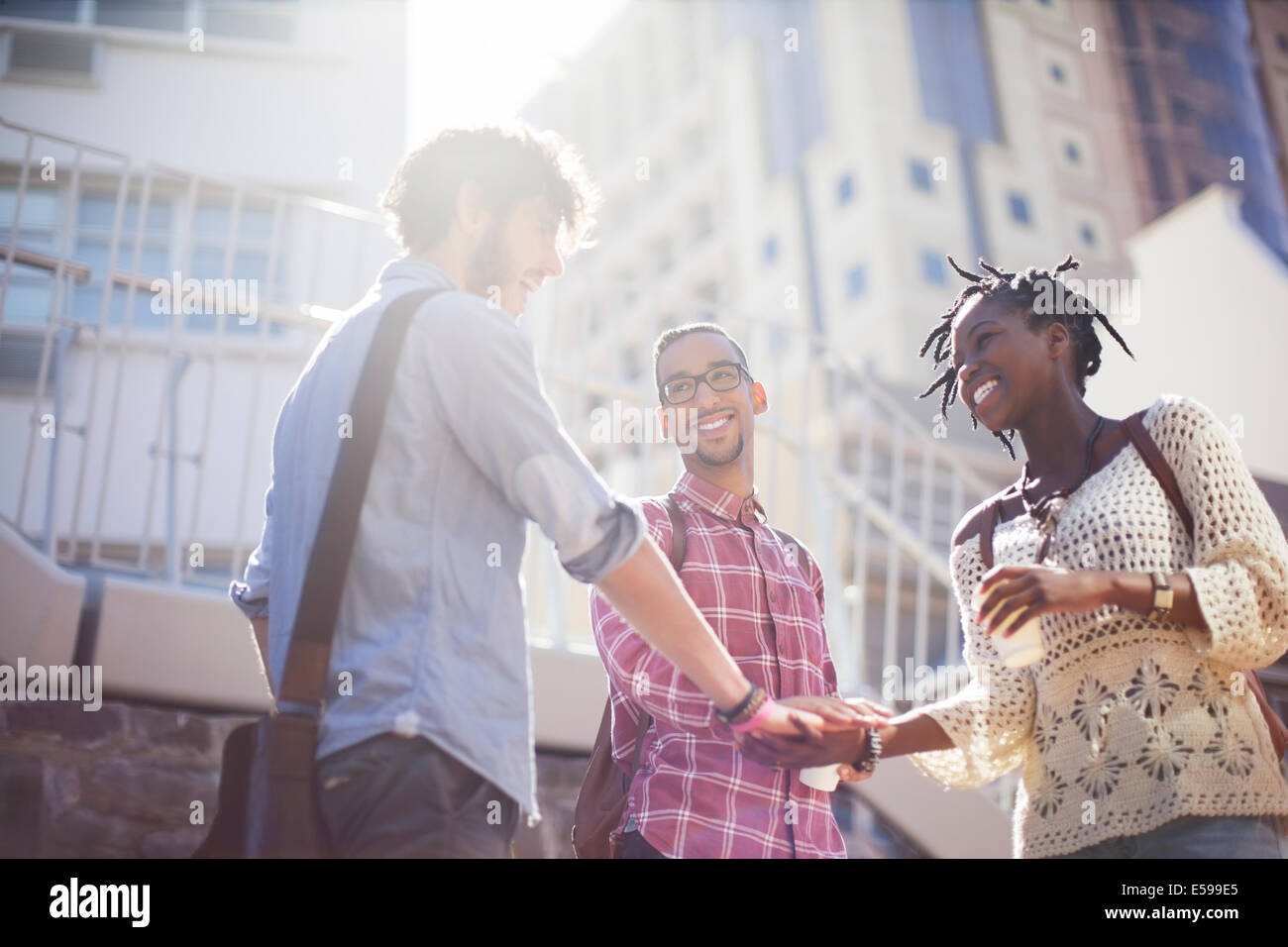 People shaking hands on city street - Stock Image