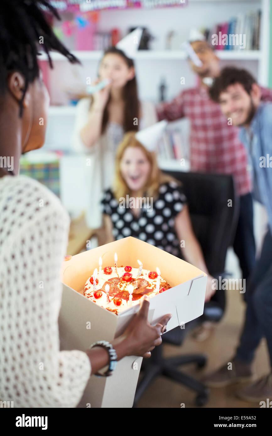 People celebrating birthday in office - Stock Image