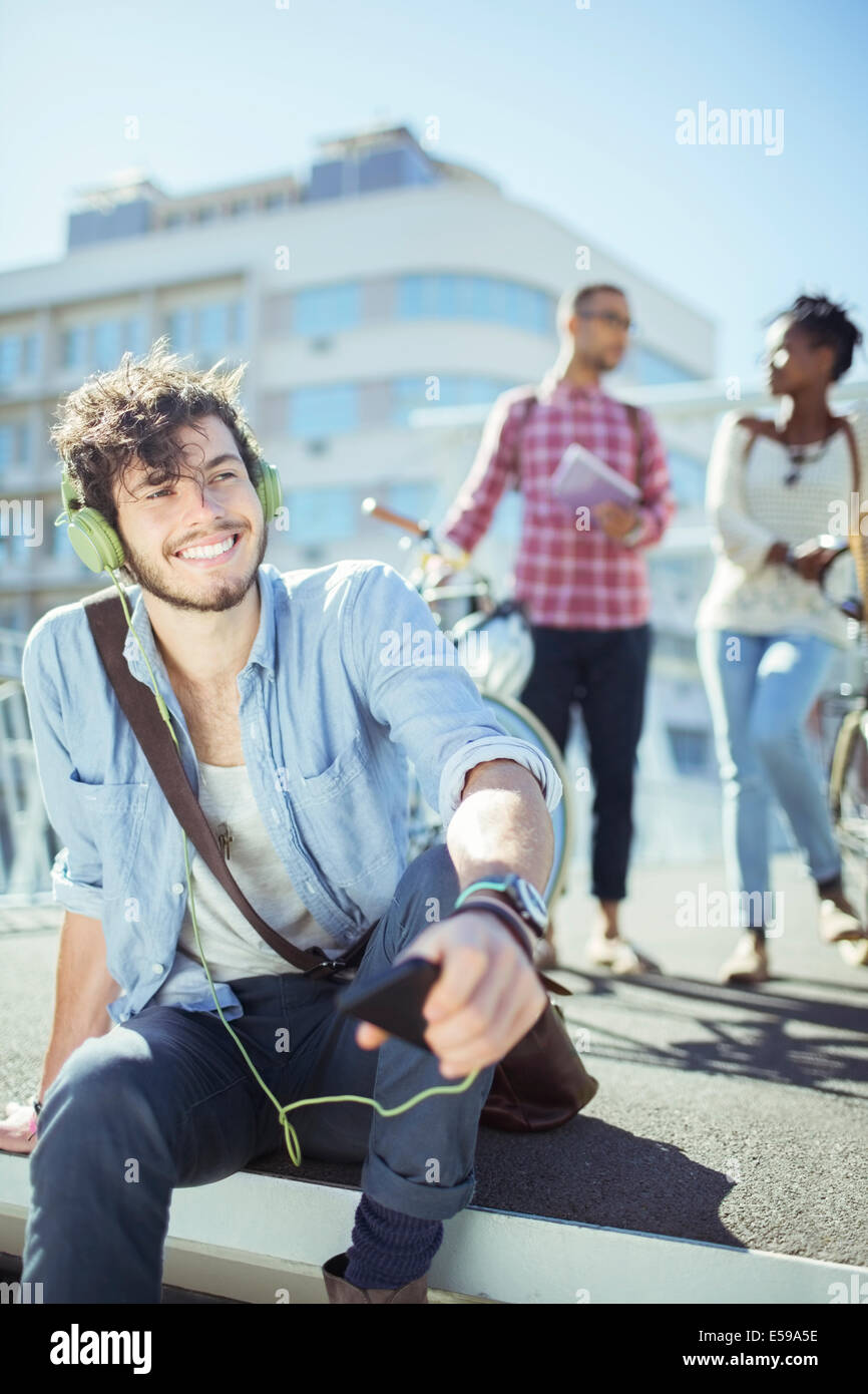 Man listening to mp3 player on city street - Stock Image