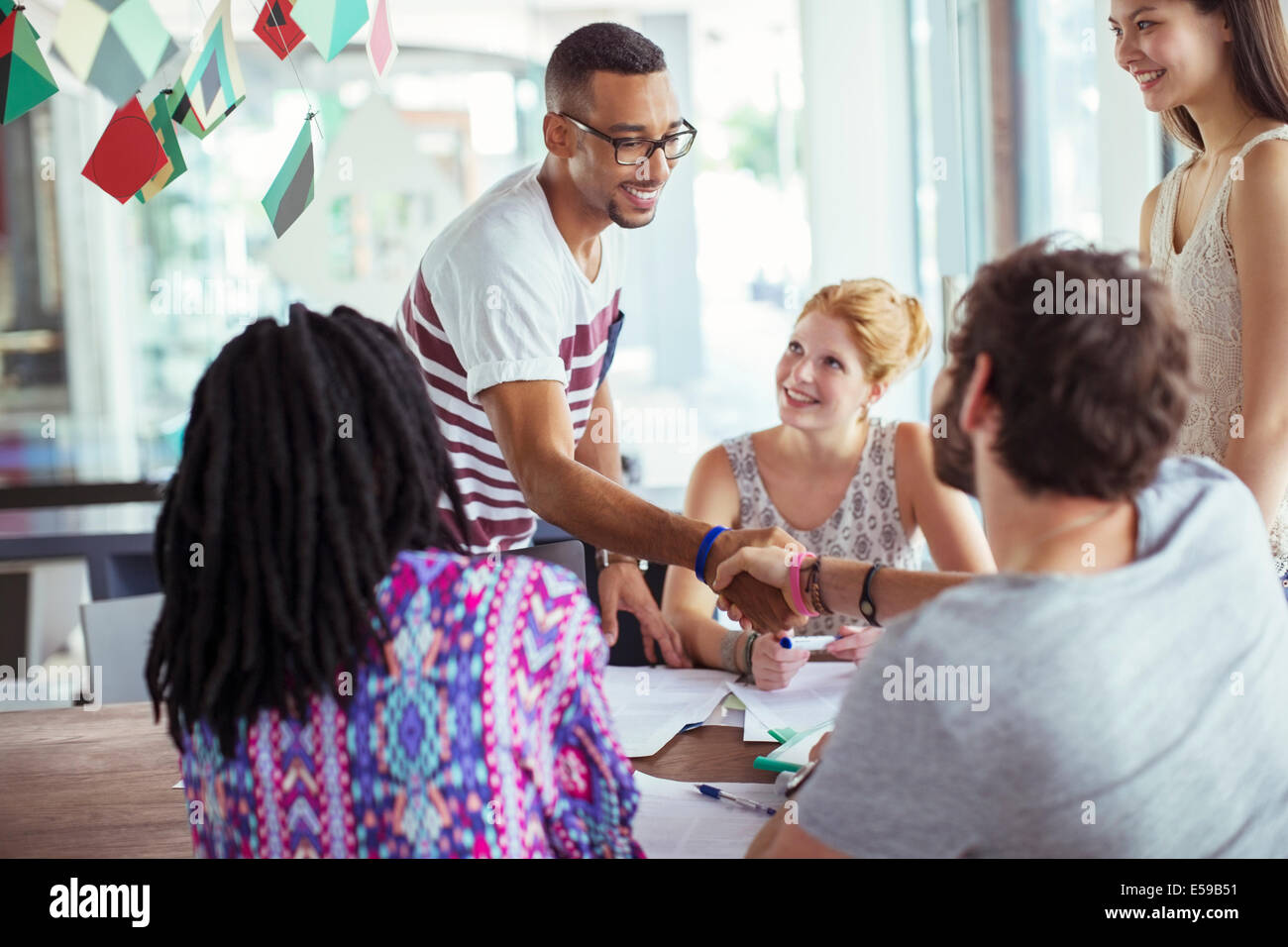 People shaking hands in office - Stock Image