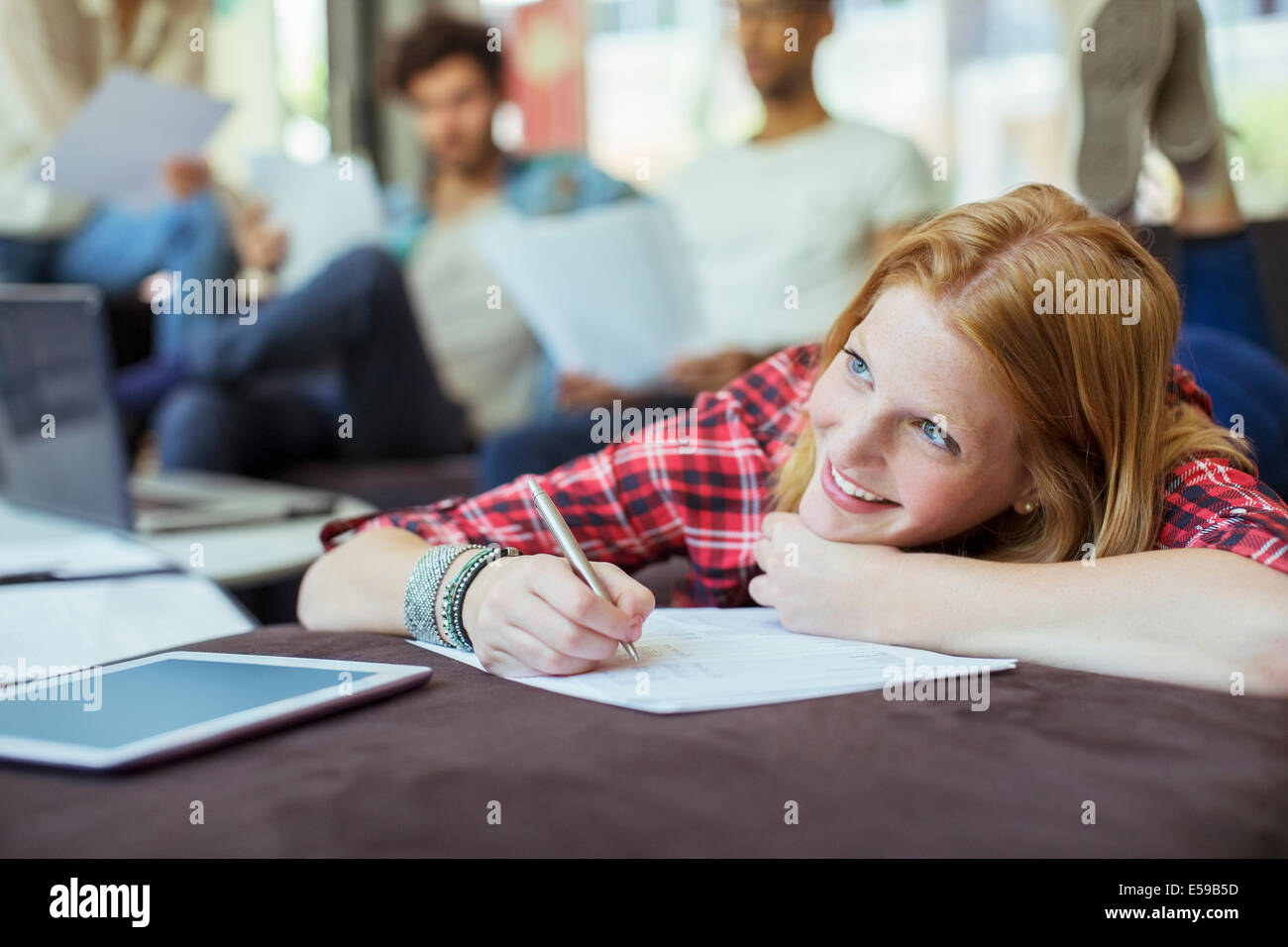 Woman writing in office - Stock Image