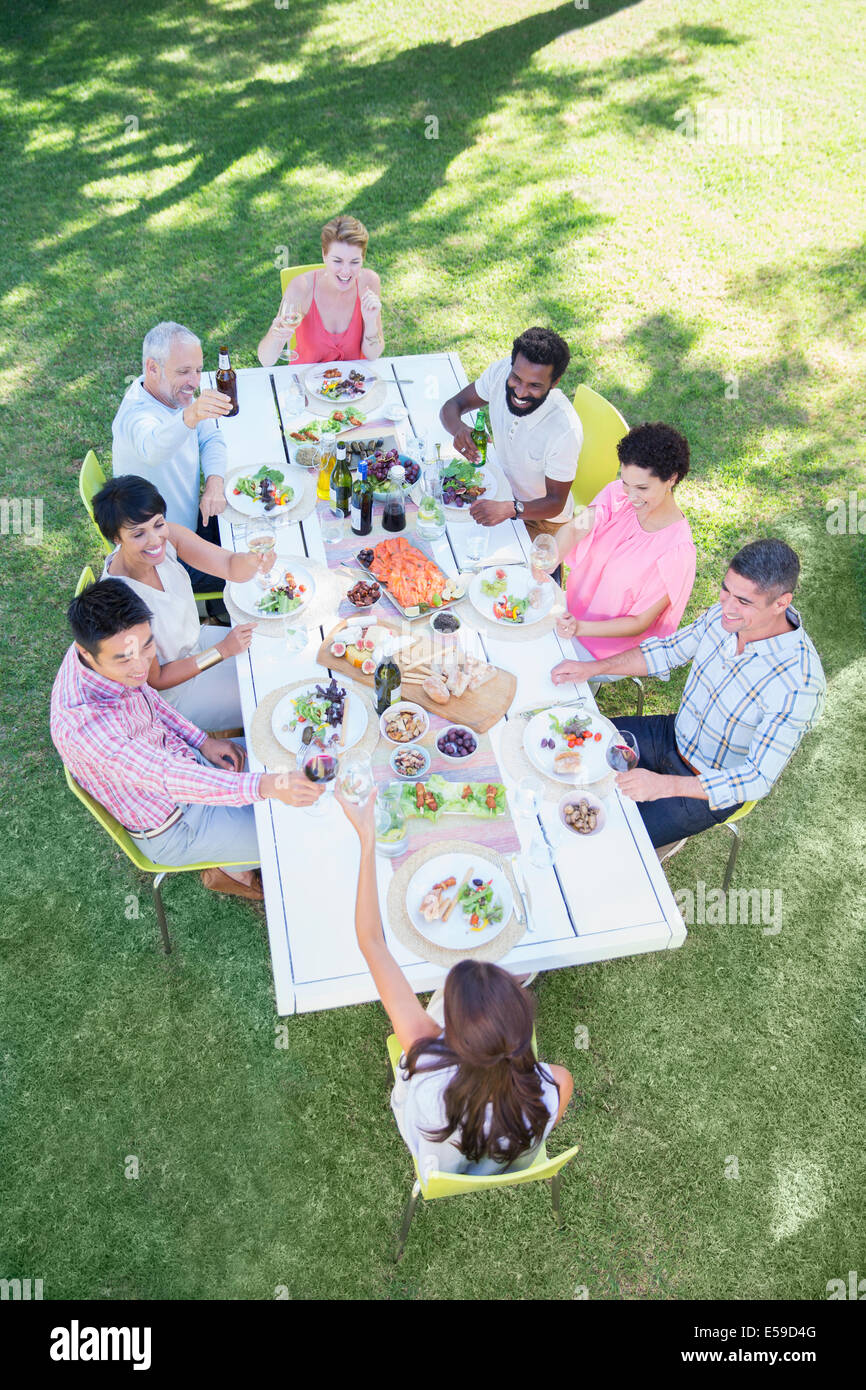 Friends eating together at table outdoors - Stock Image