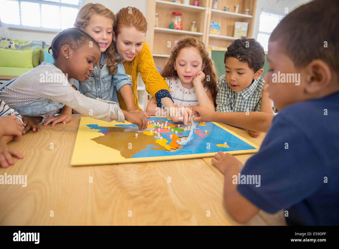 Children and teacher playing in class - Stock Image