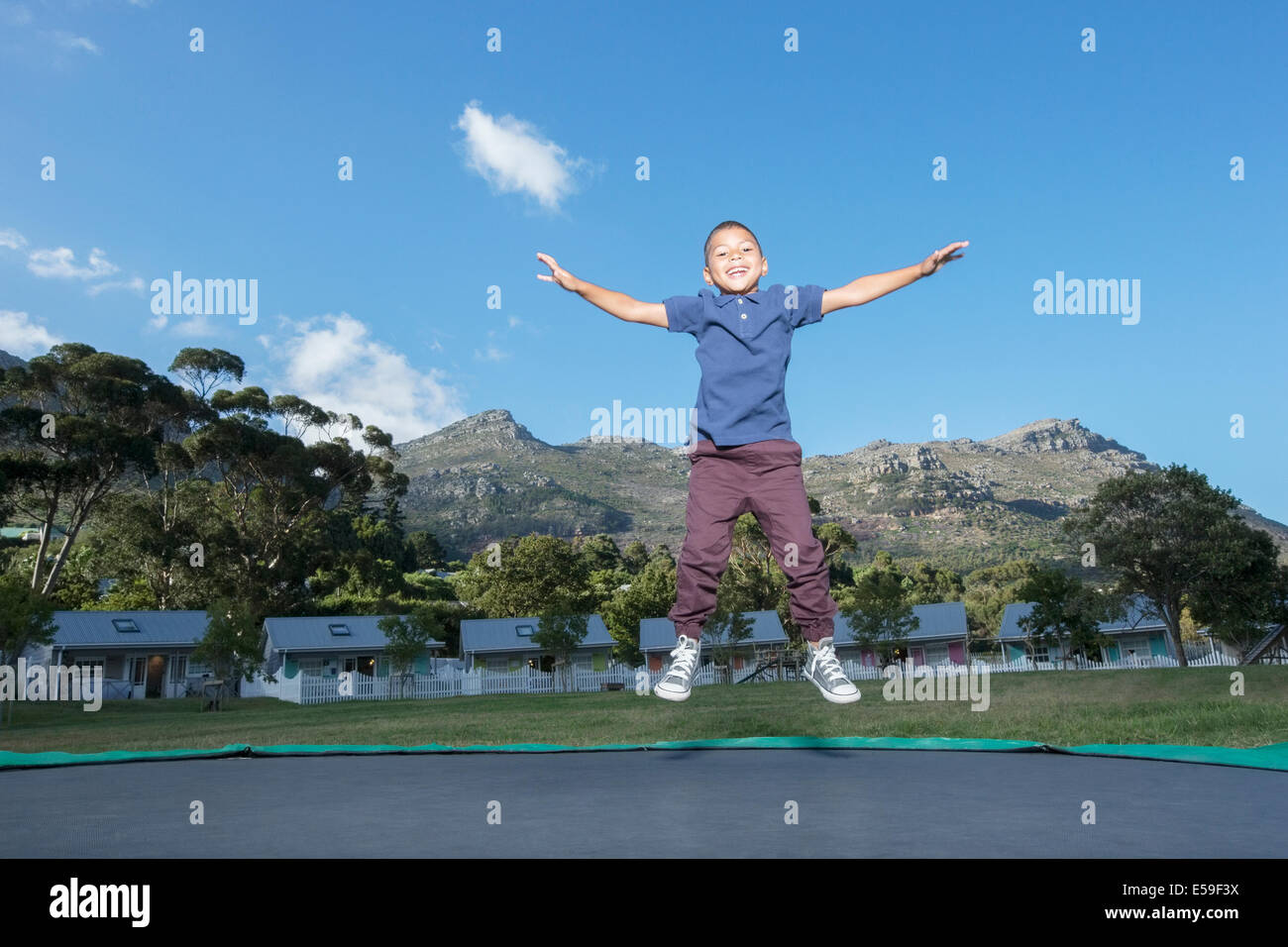 Boy jumping on trampoline outdoors - Stock Image