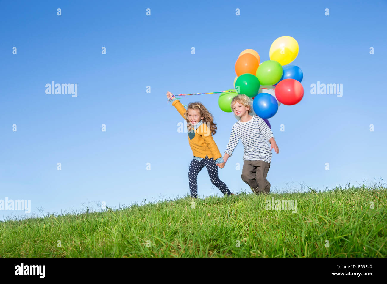 Children with bunch of balloons on grassy hill - Stock Image