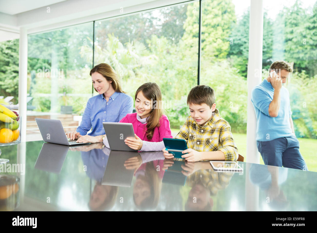 Family using technology in kitchen - Stock Image
