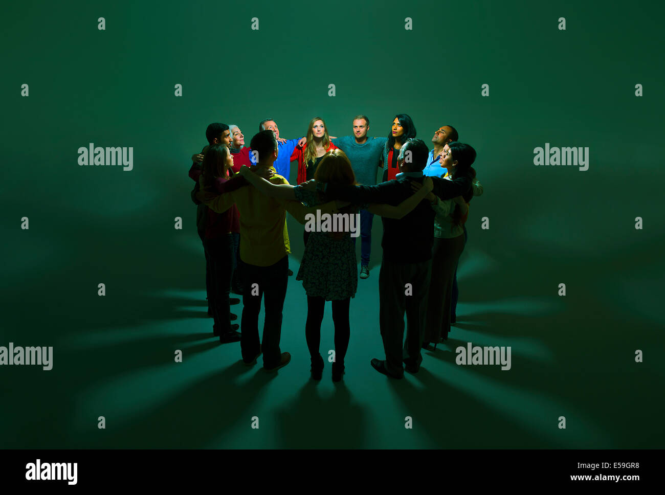 Business people in circle around bright light - Stock Image