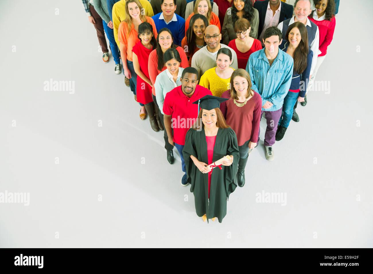 Diverse crowd behind confident graduate - Stock Image