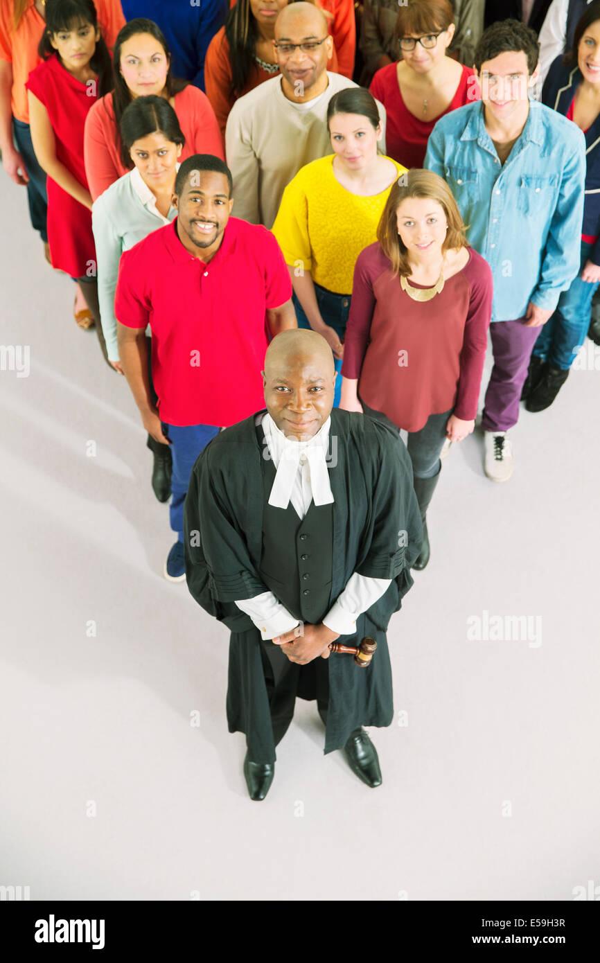 Portrait of crowd behind confident judge - Stock Image