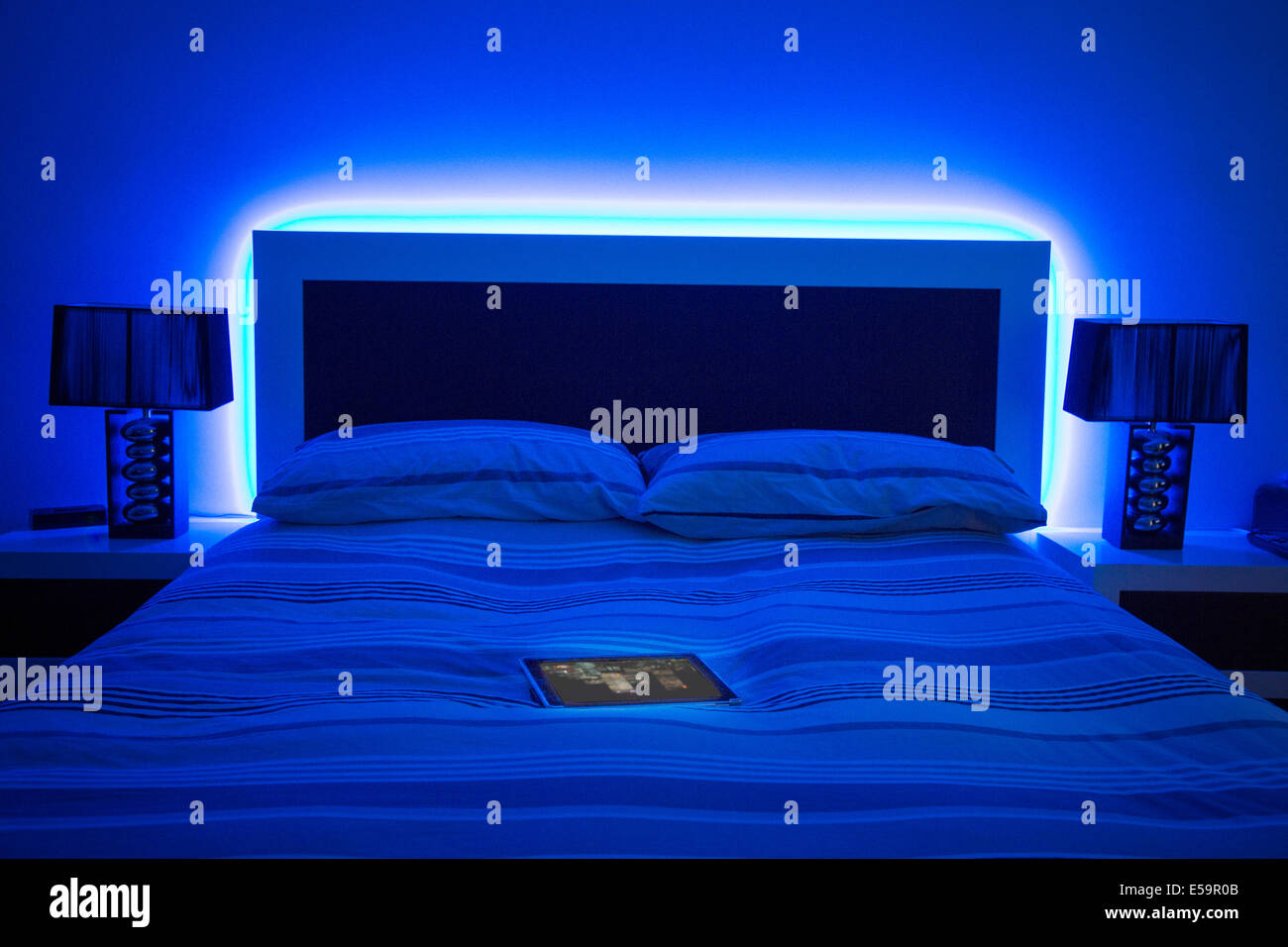 digital tablet on glowing bed - Stock Image