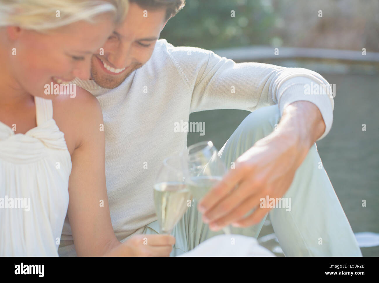 Couple toasting each other with champagne outdoors - Stock Image