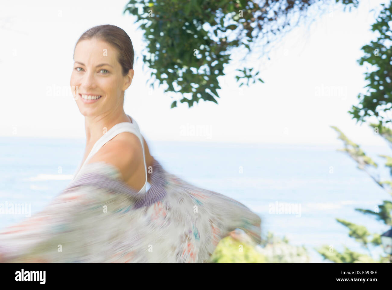 Blurred view of woman spinning outdoors - Stock Image