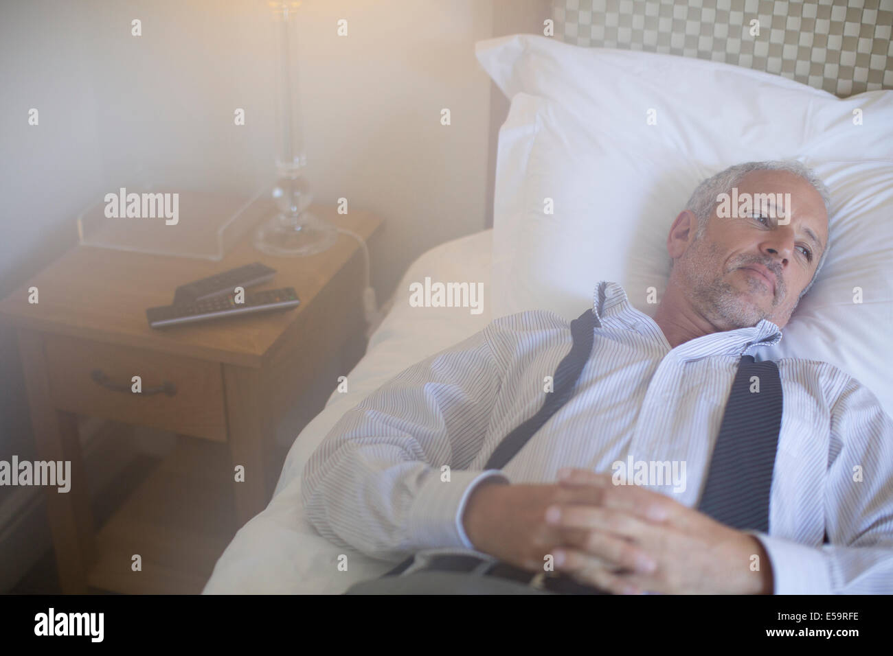 Businessman relaxing on bed in hotel room - Stock Image