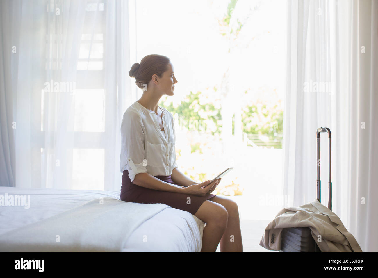 Businesswoman using digital tablet in hotel room - Stock Image
