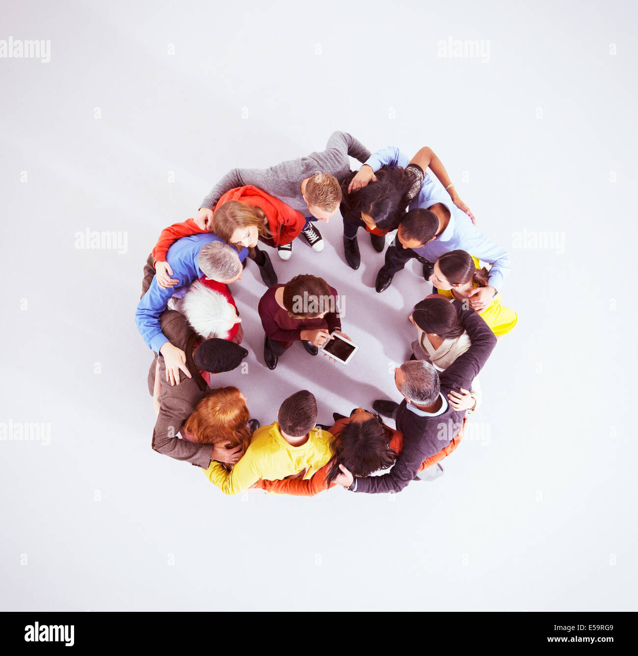 Business people huddled around woman with digital tablet - Stock Image