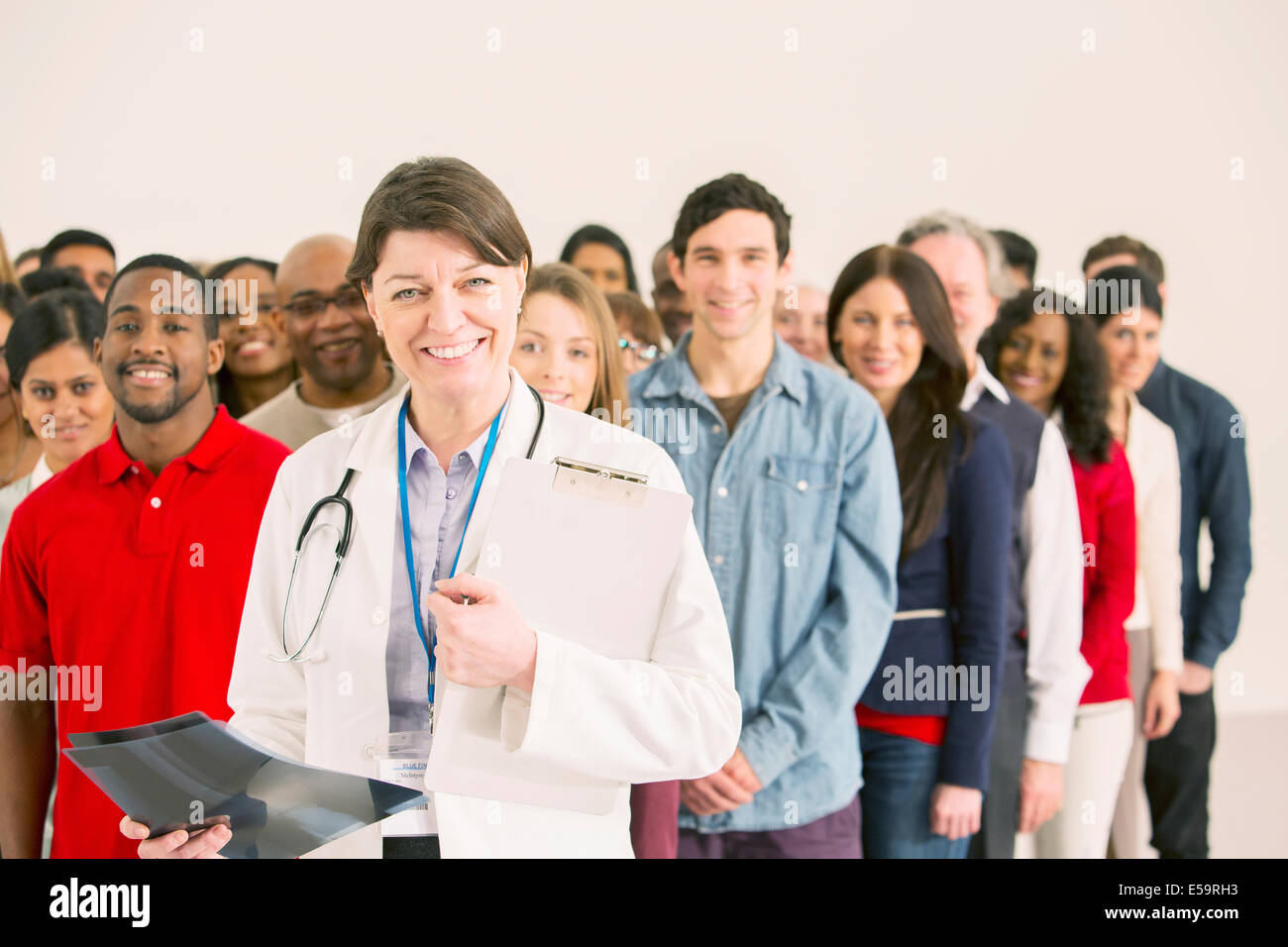 Crowd behind confident doctor - Stock Image