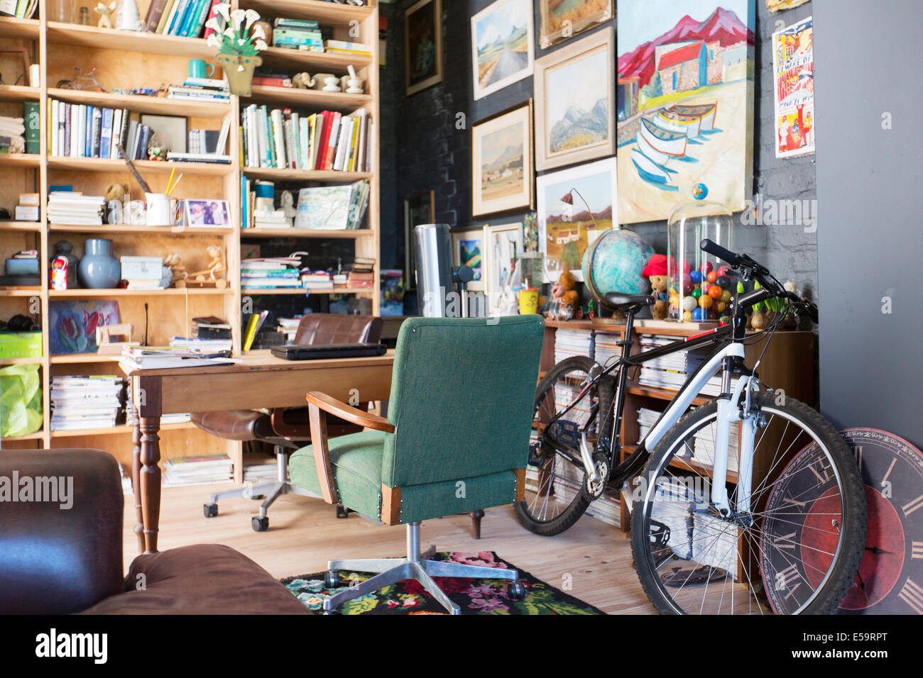 Desk, bookshelves and bicycle in study - Stock Image