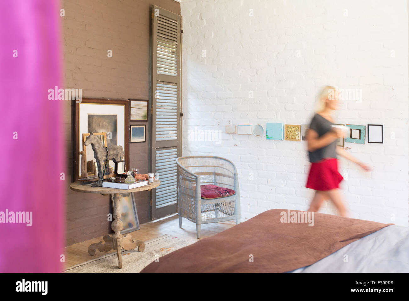 Blurred view of woman walking in bedroom - Stock Image