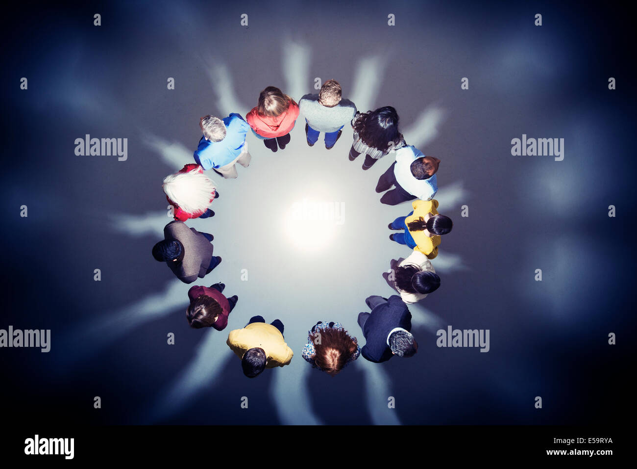 Business people with backs to bright light - Stock Image