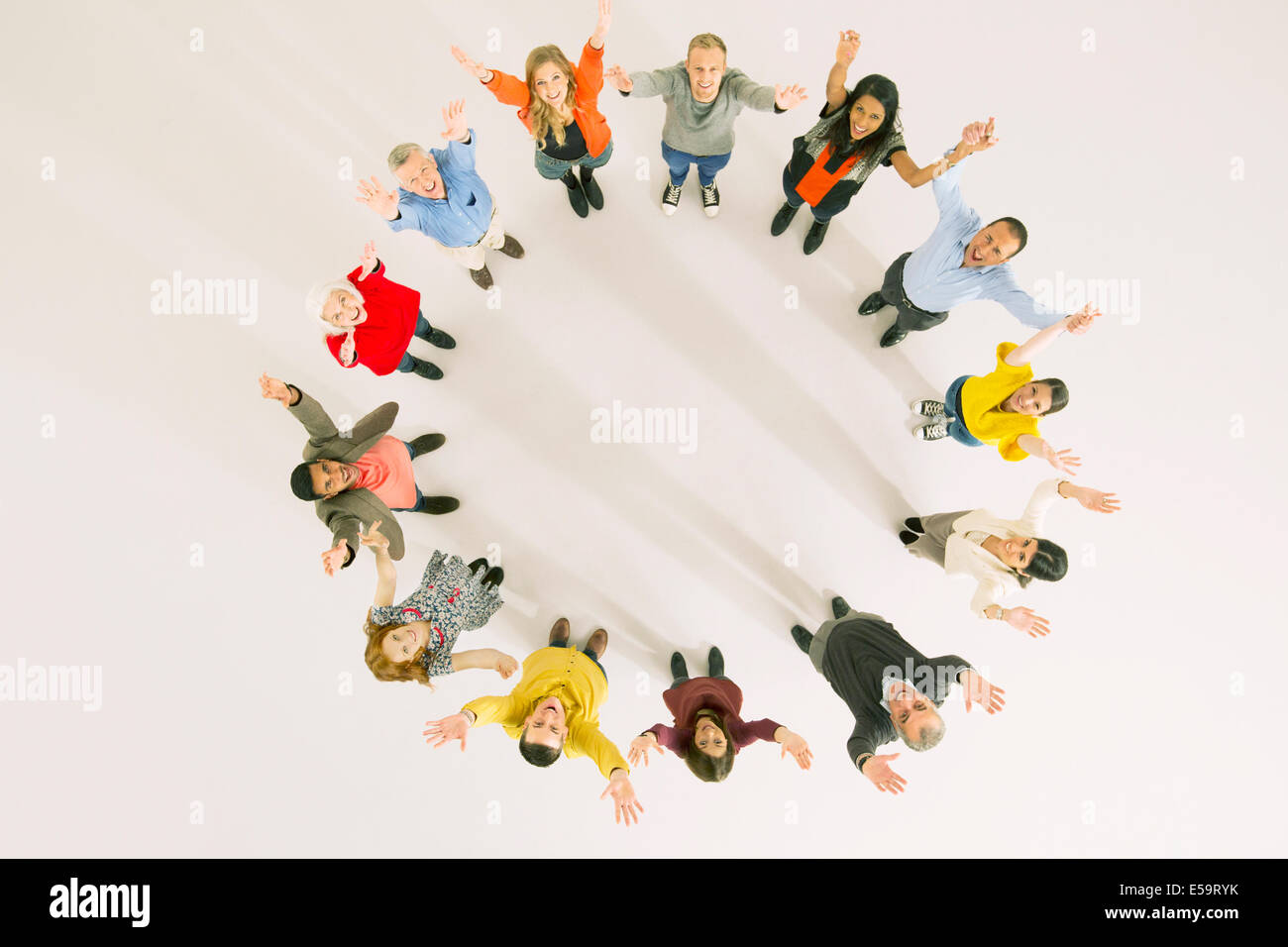 Business people with arms raised in circle - Stock Image