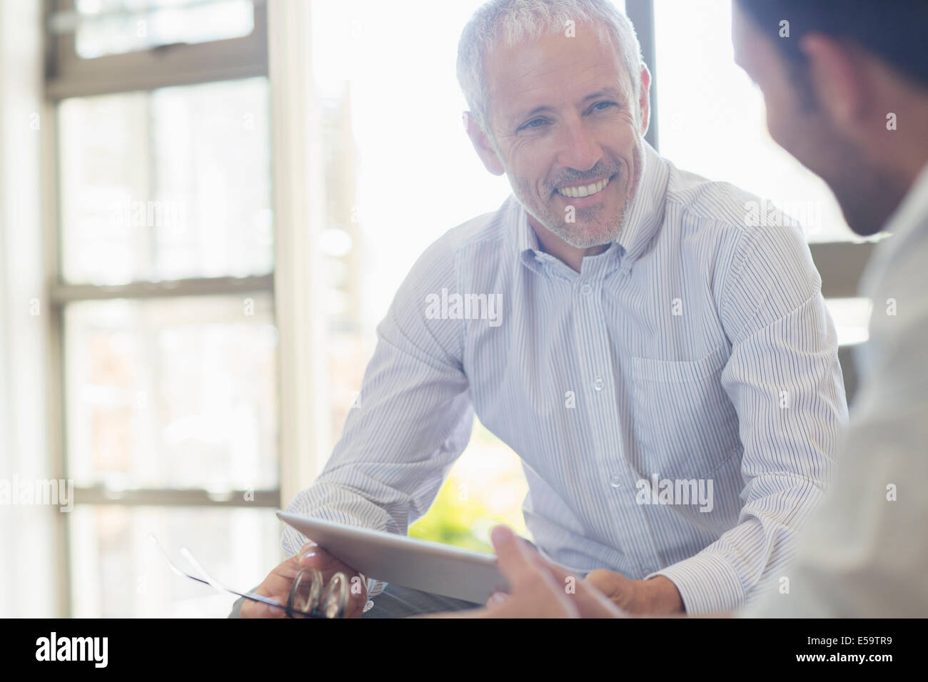 Businessmen laughing together in office - Stock Image