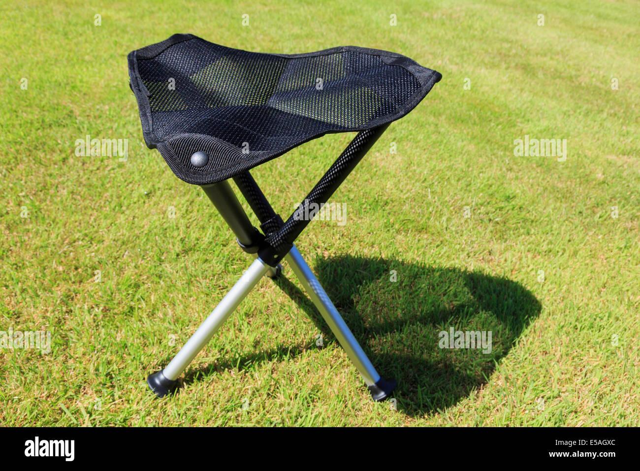 Folding Portable Three Legged Tripod Camping Stool With A Triangular Mesh  Seat On Grass In Sunshine