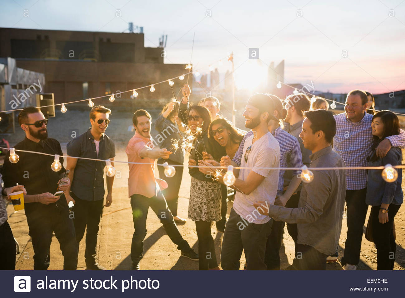 Friends with sparklers enjoying urban rooftop party - Stock Image
